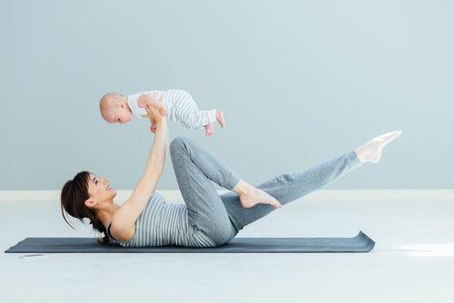 mujer haciendo pilates con su hijo